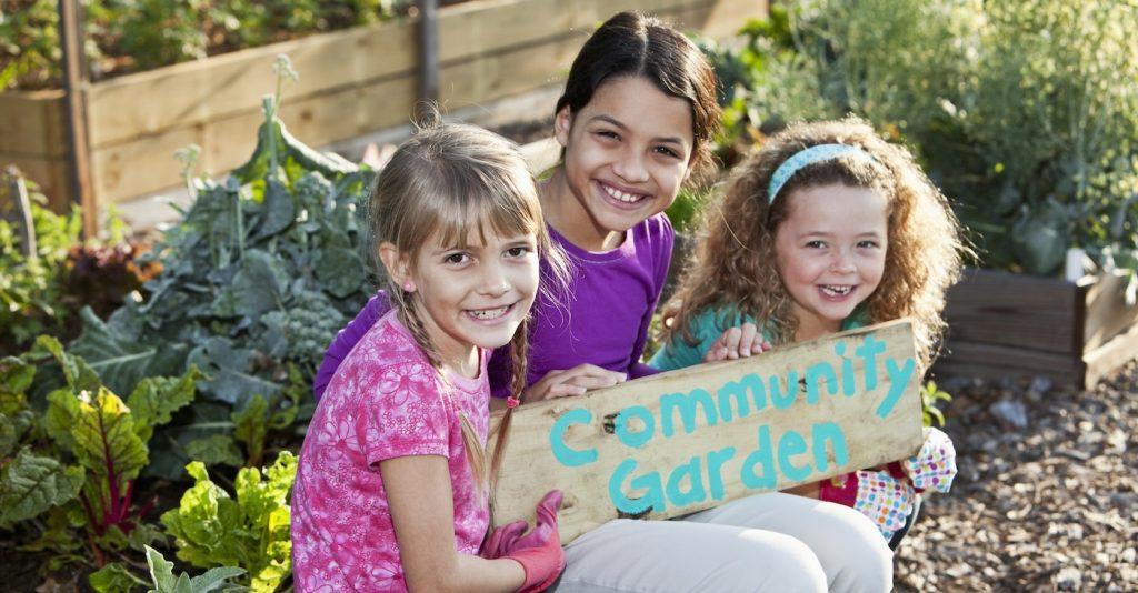 Girls (6 to 11 years) at community garden, holding sign. Main focus on blond girl in foreground.